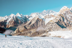 Snow and Mountains View and small Body of Climber walking Royalty Free Stock Photo
