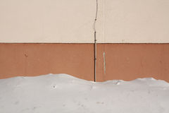 Snow near brown house wall. Royalty Free Stock Image