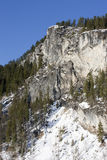 Snow near granite cliff. Royalty Free Stock Photos