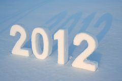 Snow number 2012. Numbers 2012 cut out from snow crust on snowdrift with blue shadows Royalty Free Stock Photo