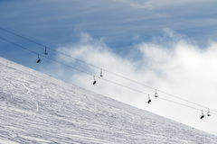 Snow off-piste ski slope and chair-lift in fog Royalty Free Stock Image