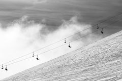 Snow off-piste ski slope and silhouette of chair-lift in fog Stock Photos