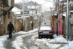 Snow in an old and unmodernised part of Baku, with coloured houses, a lone figure, and a car. An area a few miles north of the centre of Baku, capital city of Stock Photography