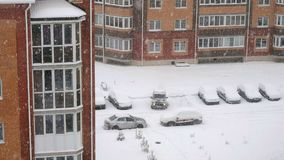 Snow over multi storey houses. City landscape during the snowfall - residential multi-storey houses with smoke from the pipes next to the yard with cars stock video