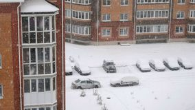 Snow over multi storey houses. City landscape during the snowfall - residential multi-storey houses with smoke from the pipes next to the yard with cars stock footage