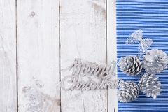 Snow painted pine cones on rustic white wood table. Christmas decoration background Stock Images