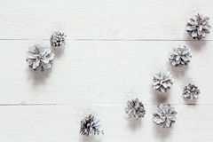 Snow painted pine cones on rustic white wood table. Space for te Royalty Free Stock Photo
