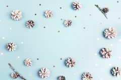 Snow painted pine cones with stars and copy space on blue background. Winter decoration background. Top view, flat lay stock photos