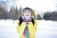Snow on the palms. A girl in a park in the yellow jacket blows snow from the palms Stock Photo
