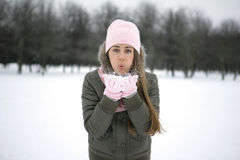 Snow on the palms. A girl in a park in the jacket blows snow from the palms Royalty Free Stock Photography