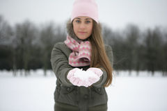 Snow on the palms. Girl in a park in winter snow on a palm Royalty Free Stock Photos