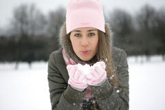 Snow on the palms. A girl in a park in the jacket blows snow from the palms Stock Photo