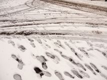 Snow on path and road outside tire marks trails foot prints floo. R background; essex; england; uk Stock Photography