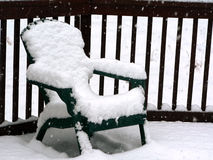 Snow on patio chair. Photo of snow on patio chair on a outside deck in the winter during a snow storm royalty free stock photos