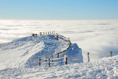 Snow peak above clouds. With wire fence stock images