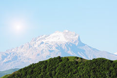 Snow peak behind green hill Royalty Free Stock Image