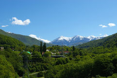 Snow peak, forest and village. At Coucasian mountain in Sochi, Russia. ViLage: Krasnaya Poliana Stock Image