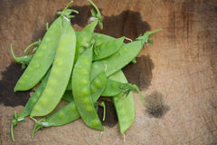 Snow peas on wooden chop board Royalty Free Stock Photos