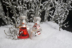 Snow people. Two miniature snow people ornaments in outdoor snow scene stock image