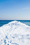 Snow pier in the sea on a sunny winter day Royalty Free Stock Images