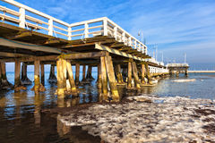 Snow pier in the sea on a sunny winter day. Stock Photos