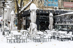 Snow piles up on a tables and chairs in a coffee bar Royalty Free Stock Photo