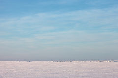 Snow plain and blue sky above a winter sea Royalty Free Stock Photo