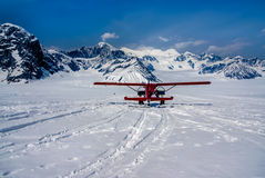 A Snow Plane Landing in a Beautiful Winter Wonderland on Top of Alaskan Mountains Stock Photo