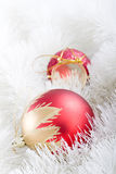 Snow Plays. Golden-red Christmas ball and red drum-toy lying in a white garland Stock Photography