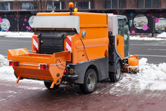 Snow plough cleaning pavements and streets  which are covered in snow and mud during heavy snowfallю Royalty Free Stock Images
