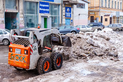 Snow plough cleaning the streets of city from snow and ice after Stock Photos