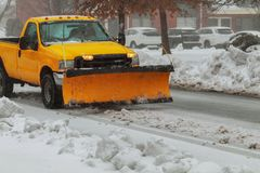 Snow plough truck clearing road after whiteout winter snowstorm blizzard for vehicle access. Snow blizzard clearing roads from snow Royalty Free Stock Images