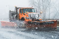 Snow plough truck vehicle ploughing streets highway during nor easter in new england connecticut. Orange plough truck removing snow from highway roads streets royalty free stock images