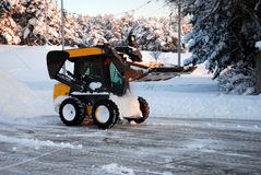 Snow plow. Plowing the snow on a square Stock Image