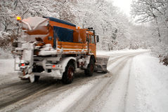 Snow plow in action. Winter service vehicle in action in a rural road Royalty Free Stock Images