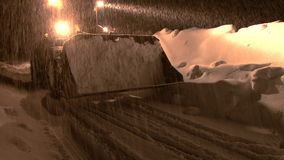 Snow plow moves down road at night during snowstorm stock video footage