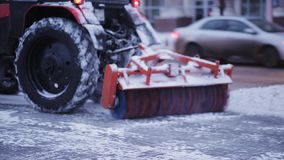 Tractor cleaning snow in the park. Snow plow outdoors cleaning street. snowplow removing fresh snow from city square. Snow plow outdoors cleaning street stock footage