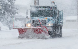 Snow plow with a red plow working in a blizzard royalty free stock images