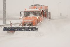 Snow plow removing snow from city road royalty free stock photos