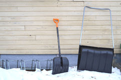 Snow plow and snow shovel leaning against a wall Stock Images