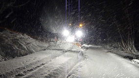 A snow plow tractor comes along in the night. Stock Photo