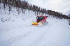 Snow plow truck clearing icy road after winter snowstorm blizzard for vehicle access Snow blower clears snow-covered streets stock photo