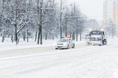 Snow plow truck convoy with patrol police car royalty free stock photography