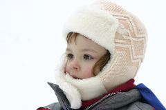 Snow portrait. Portrait of a child wearing winter fur cap isolated on white Royalty Free Stock Images