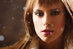 Snow princess. Close up portrait of a beautiful girl in a furcoat while snowing. Snowflakes are out of focus Royalty Free Stock Photos