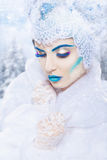 Snow queen. With a bright blue make-up on a snowy background. Fashion makeup Royalty Free Stock Photos