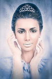 Snow queen concept headshot. Beautiful snow queen concept with hands on her face on frozen background Stock Photos