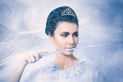Snow queen concept with an icicle in the mouth. Beautiful snow queen concept with an icicle in the mouth on frozen background Stock Photos