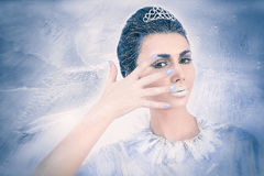 Snow queen concept looking through her fingers. Beautiful snow queen concept looking through her fingers on frozen background Royalty Free Stock Image