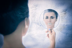 Snow queen concept looking in the mirror. Beautiful snow queen concept looking in the mirror on frozen background Royalty Free Stock Image